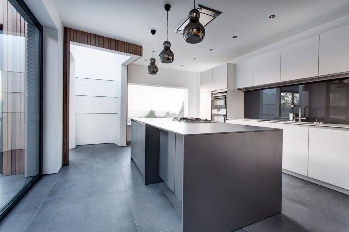exemple de cuisine grise et blanche au plancher gris foncé, déco de cuisine en longueur avec îlot central à design moderne