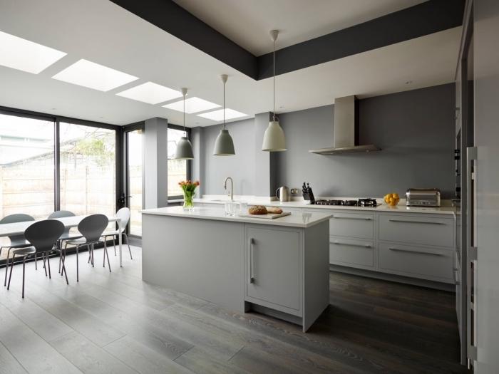 modele de cuisine moderne aux murs gris avec plafond blanc, aménagement cuisine avec table à manger et îlot
