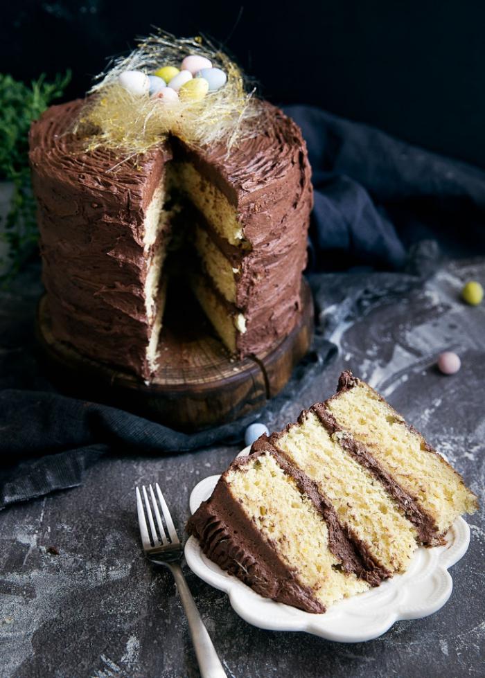 recette de layer cake nid de paques composé de trois génoises vanille fourrés de la crème au beurre et chocolat décoré d'un petit nid en sucre filé et de mini-oeufs de pâques en chocolat