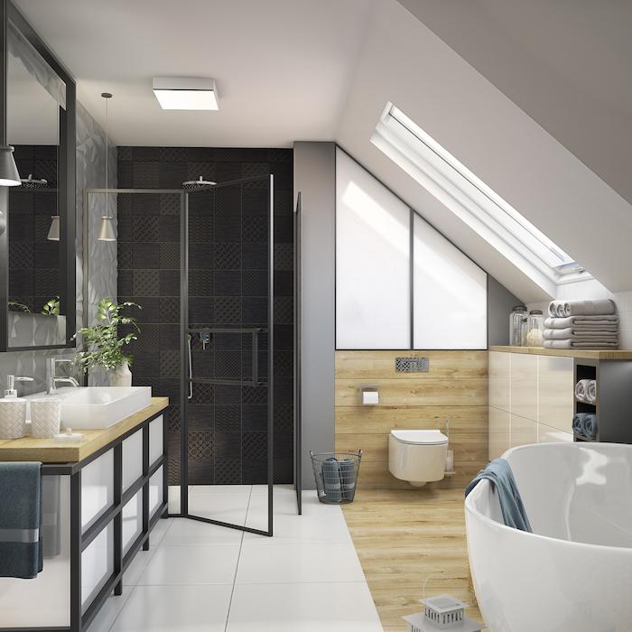 amenagement sous pente de meuble salle de bain rangement serviettes, revetement sol salle de bain bois et carrelage, baignoire et douche avec carrelage noir