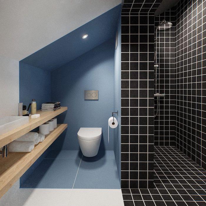wc sous pente aux murs couleur bleue et une douche en carrelage noir, meuble rangement salle de bain bois blond