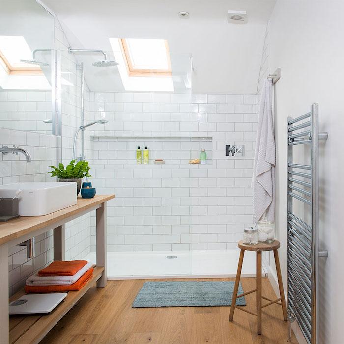 vasque à poser blanche sur meuble salle de bain bois avec étagères de rangement, parquet bois, douche avec carrelage blanc