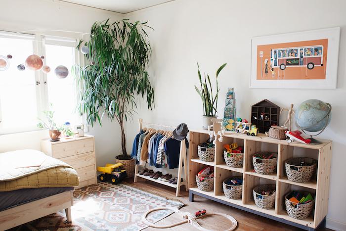 etagere meuble rangement jouet en bois avec paniers pour ranger les jouets, murs blancs, grande plante verte, tapis coloré, lit en bois, dressing enfant ouvert