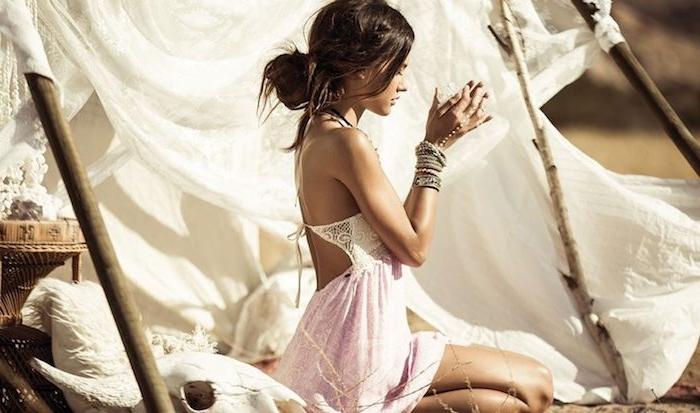 Image robe boheme longue, robe hippie chic dentelle style gitan, chignon bas, accessoires hippie, femme assise devant un tente, vie gitane romantique