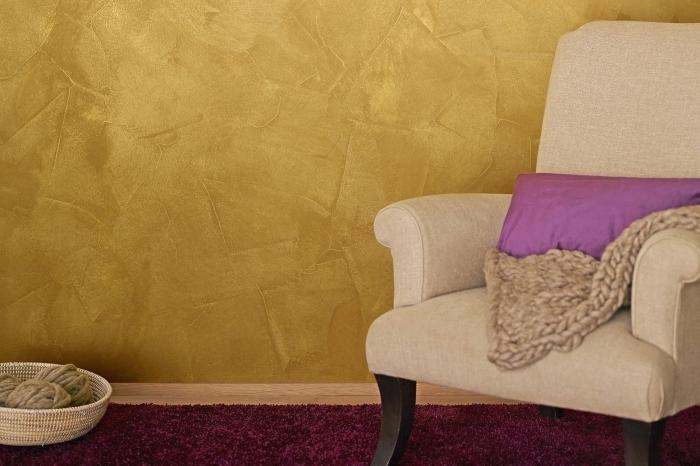 revêtement mural à effet sablé, décoration salon aux murs jaune moutarde, modèle fauteuil beige avec pieds noirs