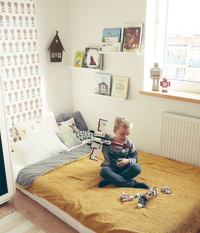 lit au sol dans un coin de la pièce, matelas au sol couvert d une couverture jaune moutarde, étagères minimalistes pour livres