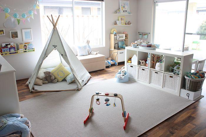 tipi enfant avec coussins et jouets à l intérieur, tapis gris d éveil, etagre basse blanche, parquet marron, petit canapé blanc bas près d une fenêtre