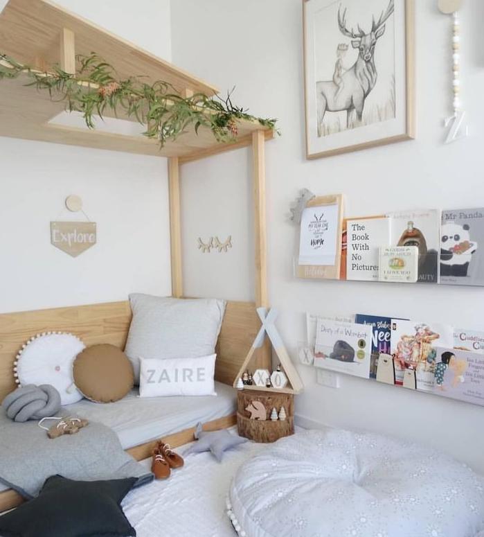 lit bois au sol avec toiture de bois, coussins enfant en couleurs neutres, étagères minimalistes sur mur blanc, pouf blanc