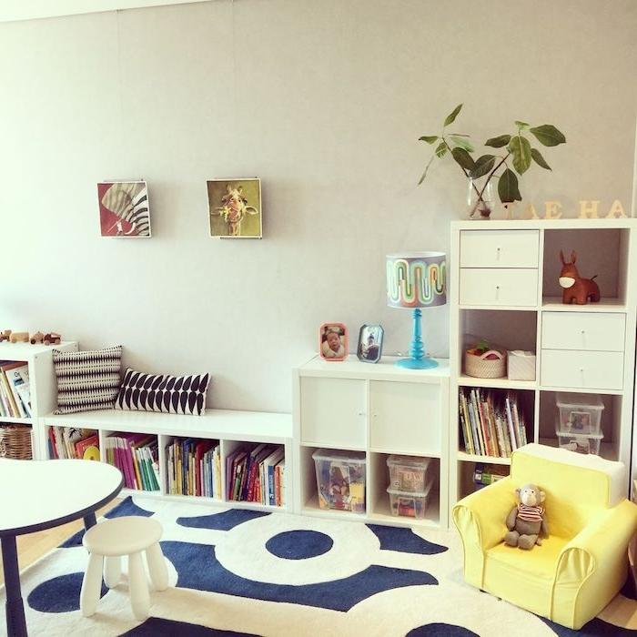 murs gris, longue etagere basse blanche pour ranger livres et boites à jouets, deco murale de cadres enfant et banc, tapis blanc et bleu marine, fauteuil jaune bas, table et tabouret bas
