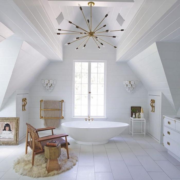 éléments en laiton dans une salle de bain blanche avec une baignoire design au centre, parquet blanchi, chaise sur tapis moelleux