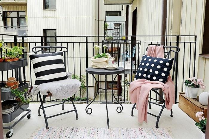 chaises metalliques noires avec deco de plaids et coussins, tapis coloré, étagère pour plantes à roulettes, pots de fleurs