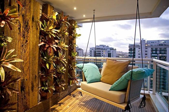 fauteuil suspendu gris décoré de coussins gris et bleu, bois composite comme revetement terrasse, mur végétal extérieur sur petite terrasse
