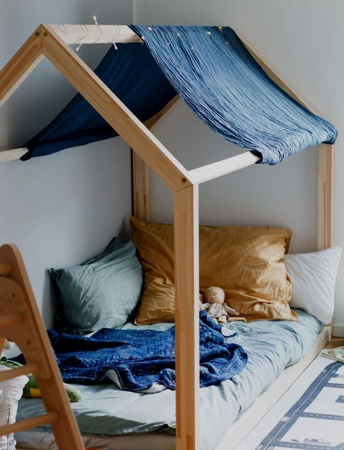 choisir un lit cabane montessori pouir la chambre enfant avec matelas gris, oreillers et coussins et ciel de lit en laine bleu marine