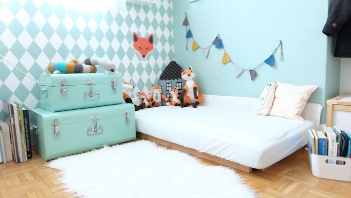 deco chambre montessori, lit au sol bois avec matelas blanc, murs bleu ciel, malles de rangement, livres au sol, deco motif renard