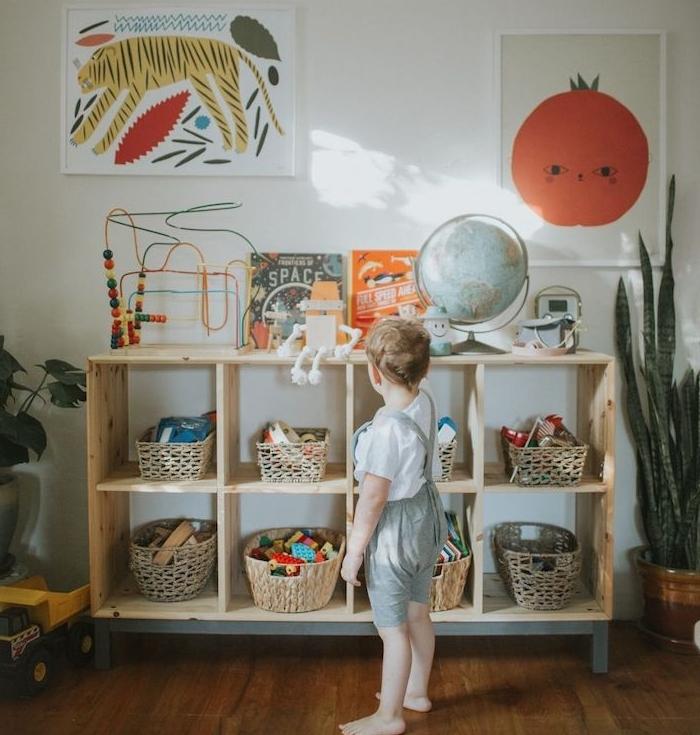 meuble bois bas avec des paniers rangement jouets, affiches muraux décoratifs animaux et plantes, jouets enfant