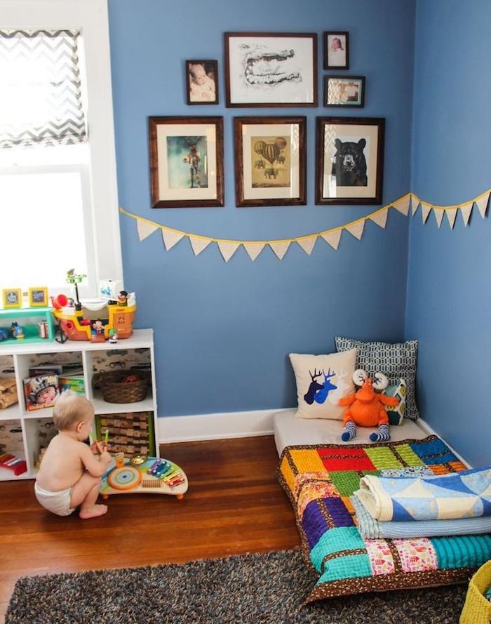 deco chambre bebe garcon en bleu avec ambiance montessori, murs bleu foncé, matelas au sol avec couverture colorée, meuble rangement jouet bas, mur décoré de cadres