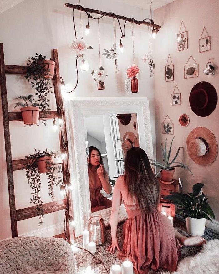 Fille qui se regarde dans le miroir et fait son maquillage, rose robe, échelle rangement fleurs, feuilles dans cadres