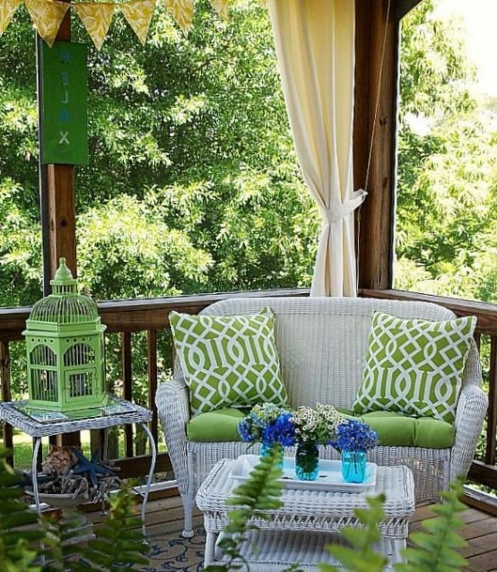 canapé et table basse en rotin avec decoration de coussins verts, cage d oiseau vert deco terrasse en bois à voiles blancs