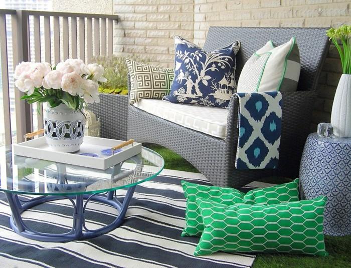 meuble balcon rotin gris, fauteul décoré de coussins blanc, bleu et vert, tapis à rayures bleu et blanc, table basse avec plateau verre, fleurs dans vase