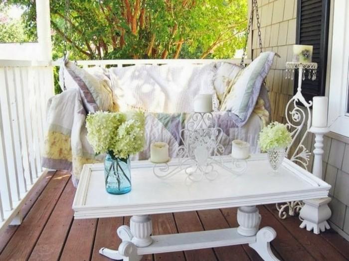 fauteuil suspendu décoré de coussins et plaid, table pour balcon basse blanche, bougeoir originale et vases de fleurs