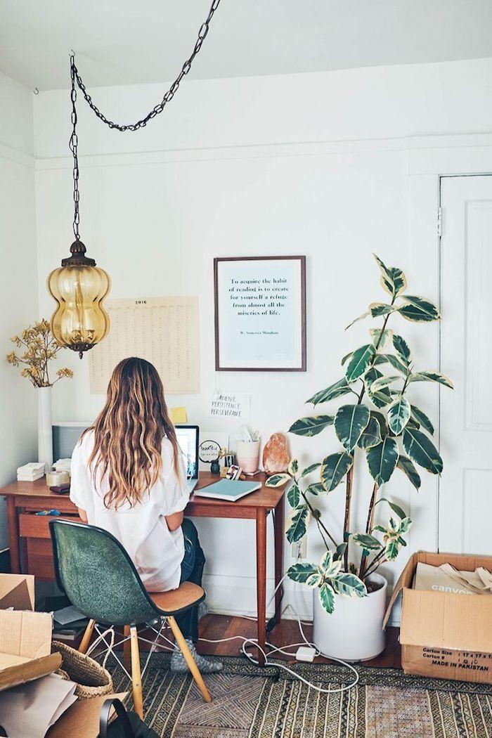 Changer d'appartement, objets en boites de carton, lustre vintage bureau rétro bois et chaise scandinave, grande plante verte, peinture murale