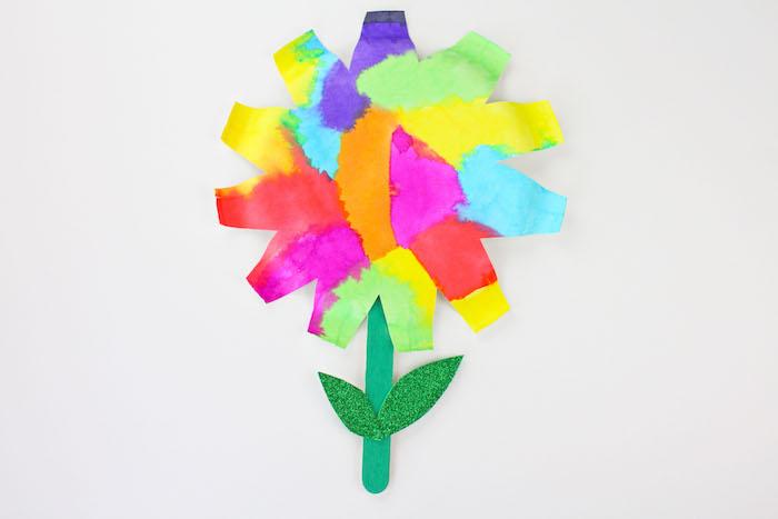 fleur colorée a faire soi meme et papier couleurs aquarelle et tige en batonnet de glace et des feuilles vertes pailletées