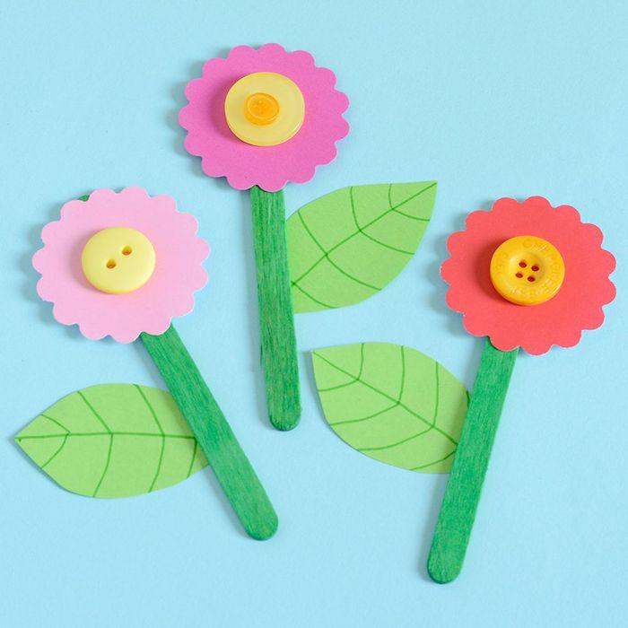 fleur en batonnet de glace, feuilles de papier et fleur en papier coloré avec centre en bouton jaune, activités manuelles maternelle