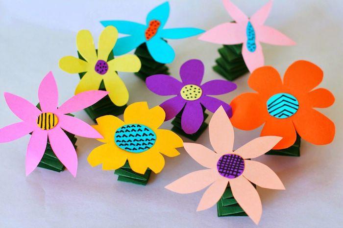 fleur en tige de papier plié en accordeon et fleur de papier coloré avec un centre en cercle de papier coloré à motifs variés