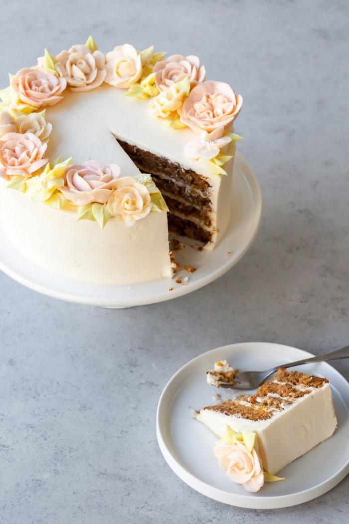 des fleurs en pâte d'amande qui décorent le dessus d'un gâteau d'anniversaire au glaçage lisse de crème beurre, gateau facile et original avec un joli décor en pâte d'amande