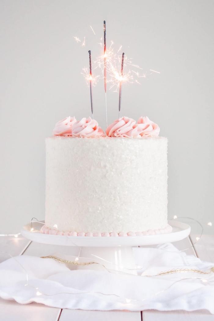 gâteau à la champagne au glaçage de crème beurre décoré avec des roses en glaçage et des bougies fontaines