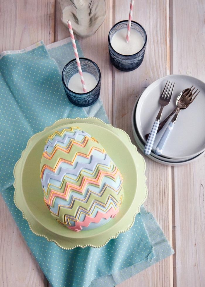 recette de paques originale pour réaliser un gâteau en forme d'oeuf recouvert de pâte à sucre, décoration de gâteau oeuf de pâques avec des motifs bandes en zig-zag en pâte à sucre
