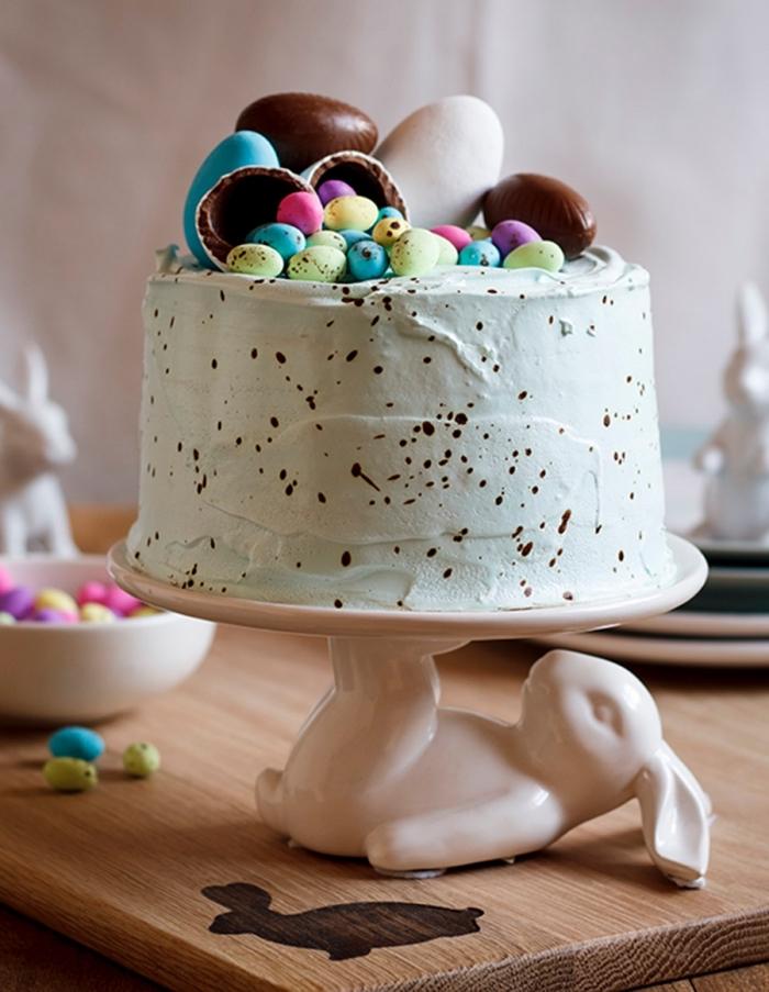 gâteau nid de pâques tacheté au glaçage de crème au beurre coloré vert pastel décoré d'œufs en chocolat, posé sur un joli présentoir à gâteau en forme de lapin