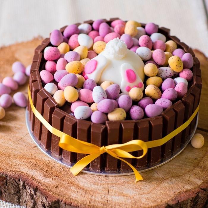 gateau de paques facile et rapide garni de barres de kit-kat et d'oeufs en chocolat pastel, gâteau queue de lapin spécial pâques posé sur un rondin de bois
