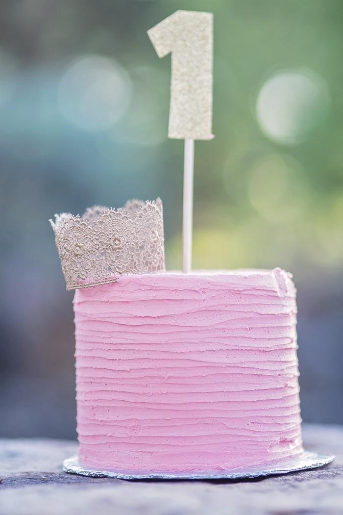gâteau de premier anniversaire au glaçage rose décoré d'une petite couronne en dentelle et d'un topper chiffre pailleté, gateau anniversaire fille 1 an