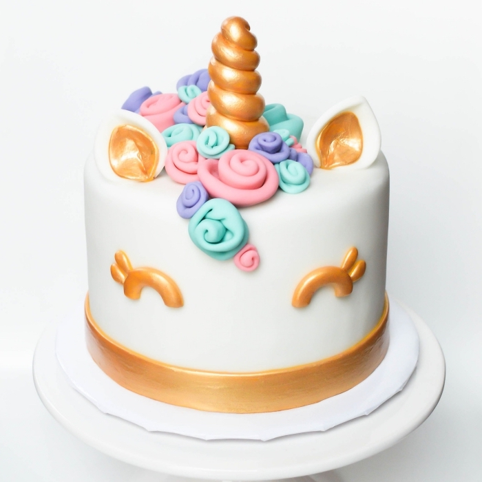 gateau anniversaire fille en forme de tête de licorne recouvert de pâte à sucre, avec des oreilles, yeux et corne dorés