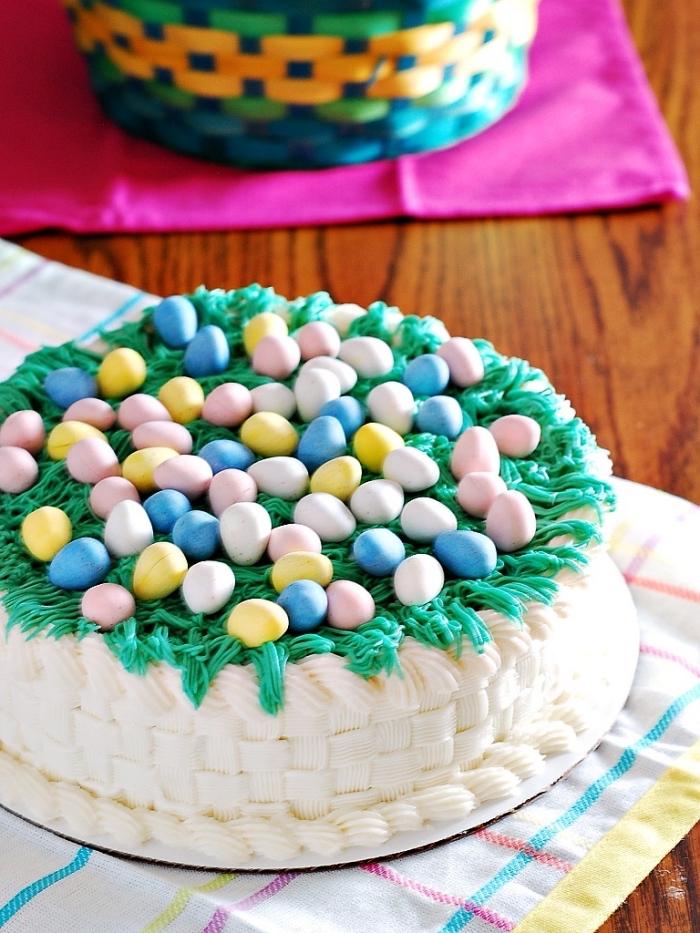 joli gâteau façon panier paques au glaçage de crème au beurre effet tissé, décoré d'herbe en glaçage vert et de petits œufs en chocolat