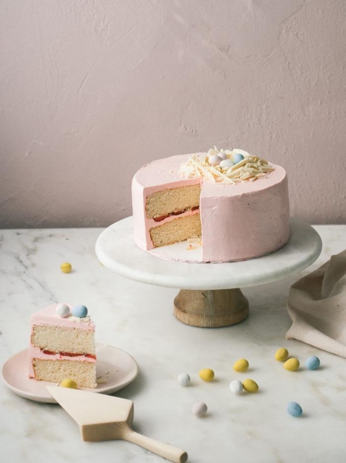 idées de desserts pour pâques, gateau nid de paques traditionnel à la vanille et à la fraise recouvert de glaçage rose de crème au beurre avec un nid en chocolat blanc