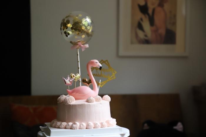 image gateau anniversaire pour fille décoré avec une figurine flamant rose, un ballon transparent à confettis dorés et des cake-toppers festifs