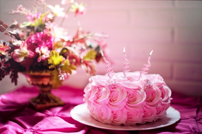un simple gateau anniversaire fille au glaçage en roses avec trois bougies zig-zag posé à côté d'un joli bouquet de fleurs
