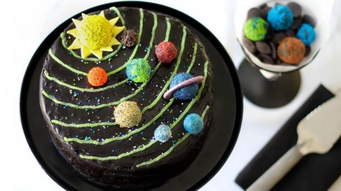gateau facile et original au glaçage noir sur thème système solaire orné de petites boules en pâte à sucre imitant les planètes