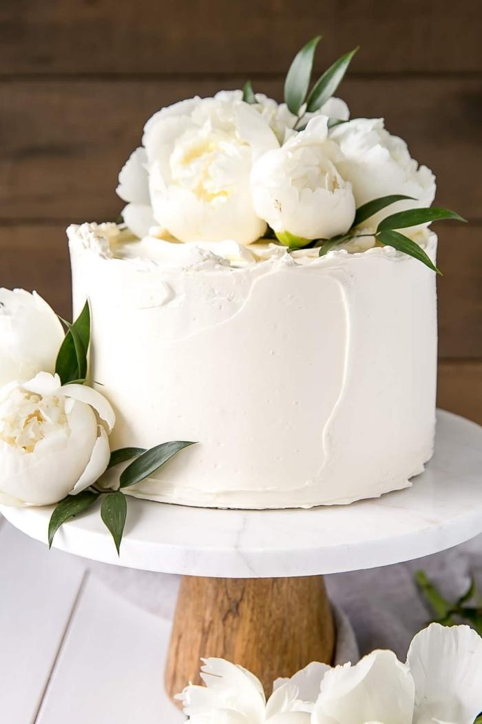 image gateau anniversaire au décor naturel de pivoines fraîches, posé sur un joli présentoir en bois et marbre