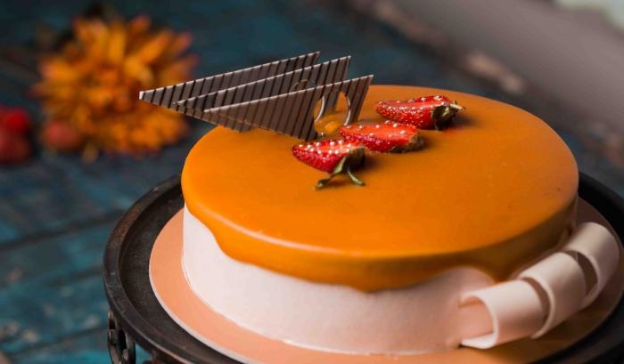 gateau d'anniversaire facile au glaçage miroir au caramel orné de tranches de fraises et de copeaux en chocolat
