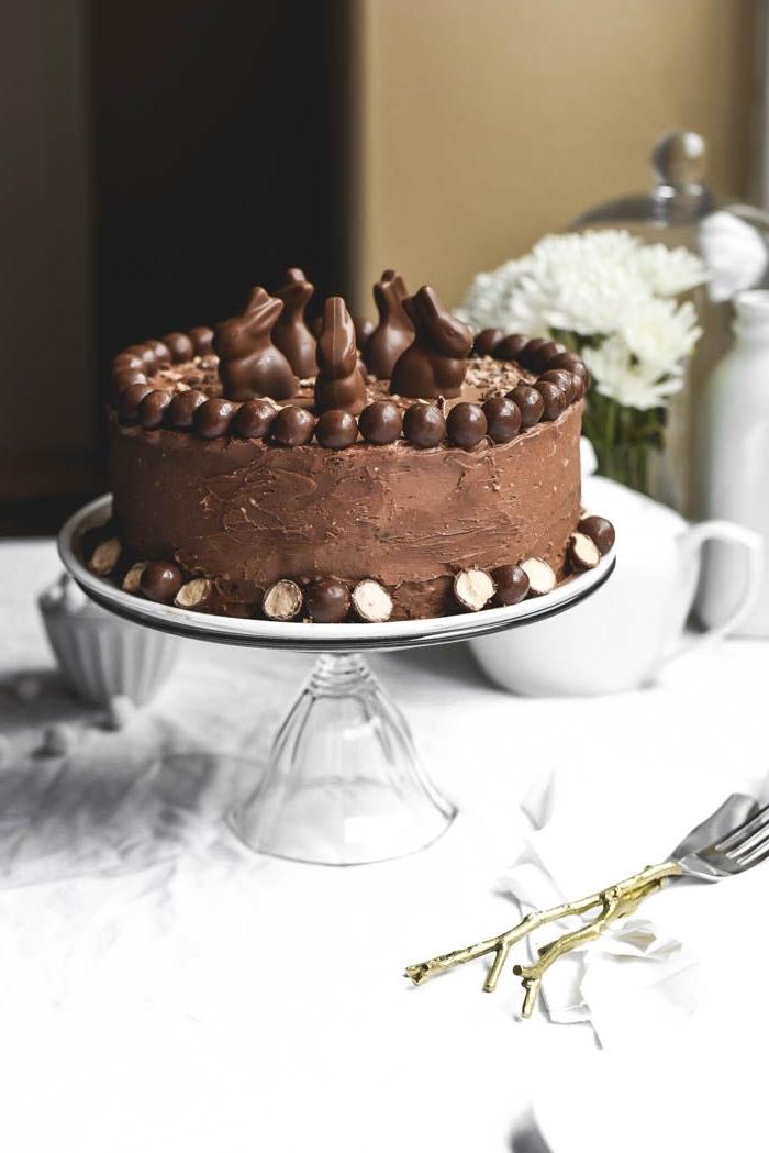 gateau de paques au chocolat facile et délicieux, gâteau moelleux recouvert de glaçage de crème beurre et chocolat, avec une décoration sur le thème de pâques de petits lapins en chocolats
