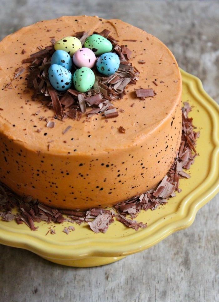 gateau nid de paques traditionnel au glaçage tacheté de crème au beurre et chocolat avec un petit nid en copeaux de chocolat et d'œufs de pâques