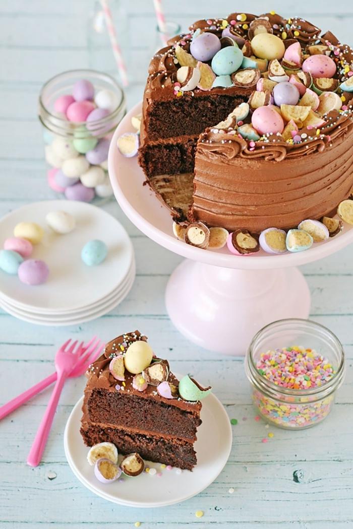 un gateau au chocolat au lait spécial pâques garni de petits oeufs de pâques en chocolat pastel composé de deux génoises au cacao fourrés de crème beurre et chocolat