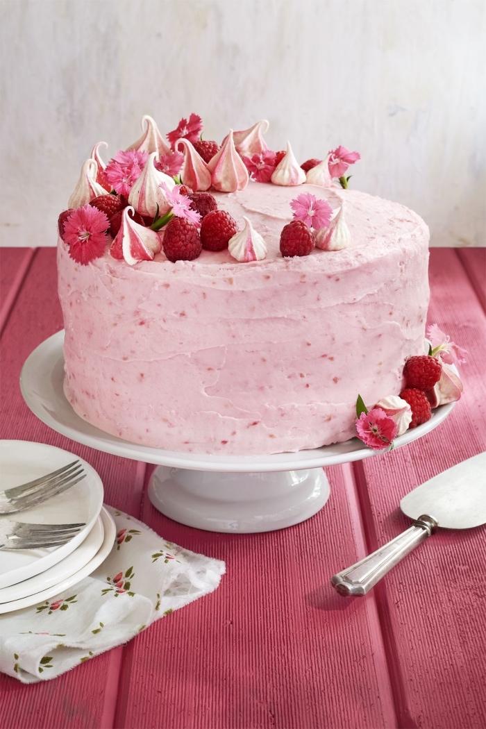 gateau anniversaire facile et original au glaçage rose à la framboise, décoré de fleurs comestibles, de meringues et de framboises fraîches