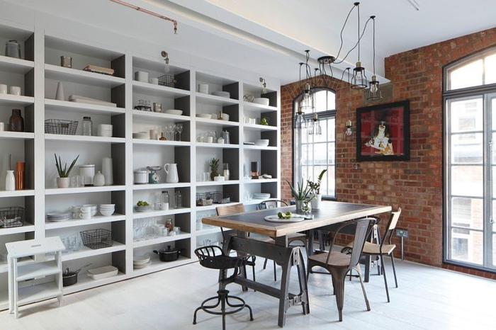 grande étagère grise, table rectangulaire en bois et métal, chaises design brut, mur en briques, fenêtres arquées