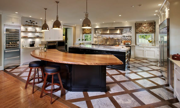 grande cuisine, tabourets en bois et cuir, ilot en forme courbée, lampes chromées, sol géométrique, réfrigérateur encastrable