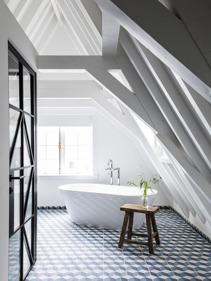 ossature apparente dans une salle de bain en blanc avec carrelage géométrique, baignoire blanche et tabouret bois, porte metal noir et vitres