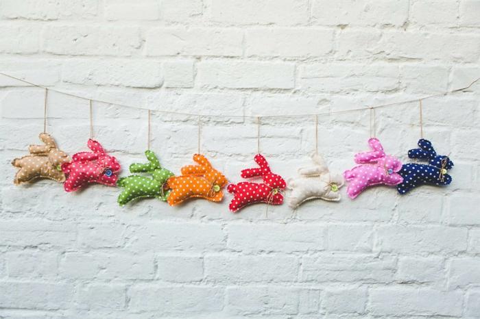 lapins colorés et pointillés en guirlande, mur en briques blanches, décoration textile à faire soi-même